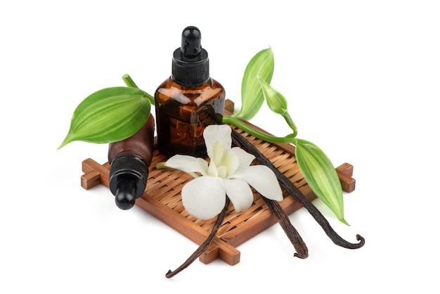 Зеленые листья ванили, сушеные стручки и извлеченные в бутылку, изолированные на белом.