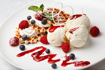 Vanilla ice cream and crispy waffles with fresh raspberries and blueberries