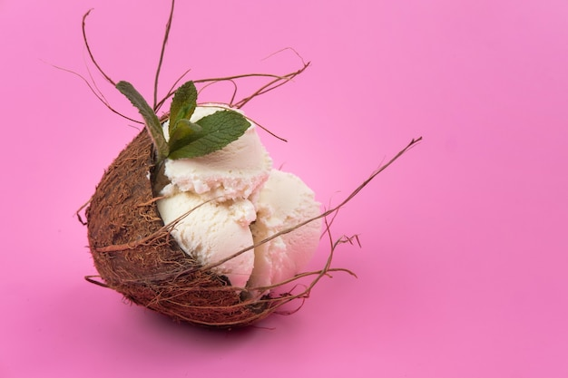 Vanilla ice cream balls in an empty coconut decorated with mint leaves on a pink background.