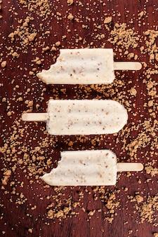 Ванильное мороженое, покрытое белым шоколадом и заправленное кремом из лесного ореха. эскимо. вид сверху