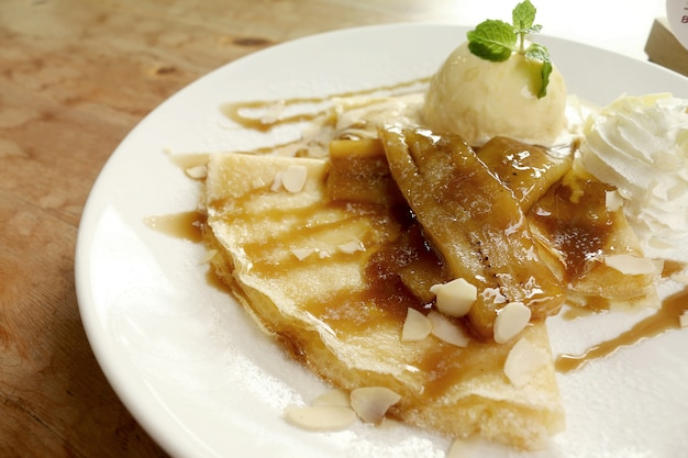 Vanilla ice cream crepes stuffed with bananas topped and caramel whipped cream