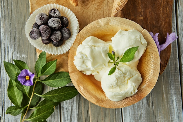 Vanilla ice cream in cup on wooden board with berries and flowers.