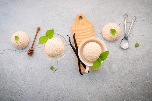 Вкус ванильного мороженого в миске со стручками ванили на бетоне.