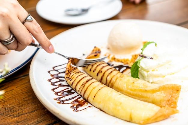 Vanilla ice-cream with banana crape and whipped cream