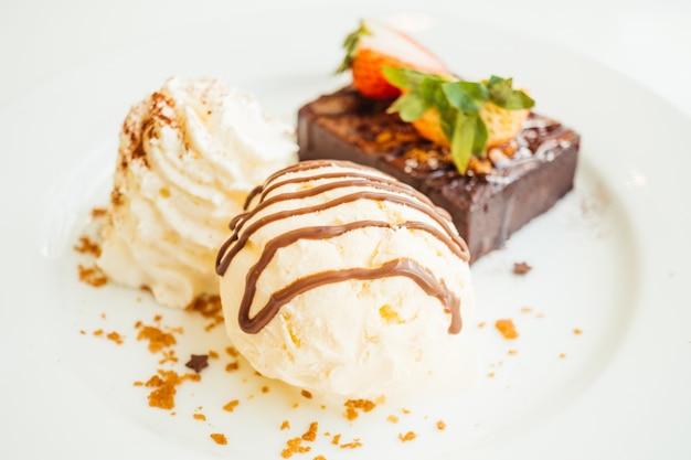 Vanilla ice cream with chocolate brownie cake with strawberry on
