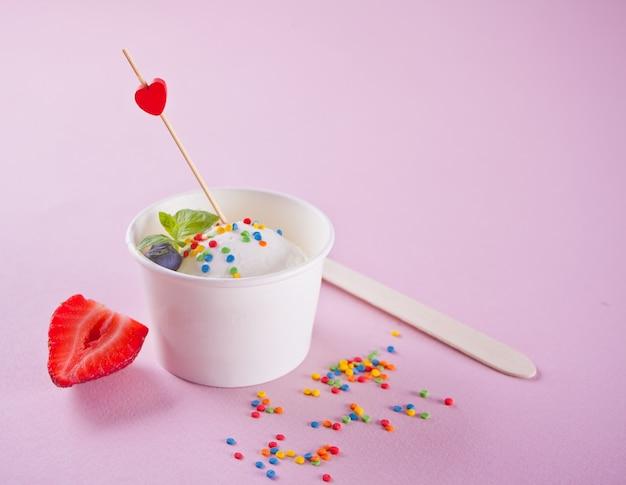Ванильное мороженое с листьями мяты, клубникой и черникой на розовом фоне