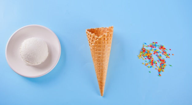 Vanilla ice cream with waffle cones and candy on the blue background