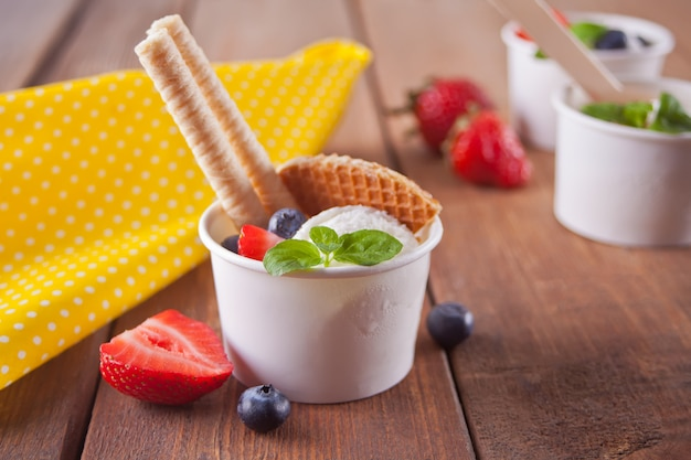 Vanilla ice cream with waffles, mint leaf, strawberries and blueberries