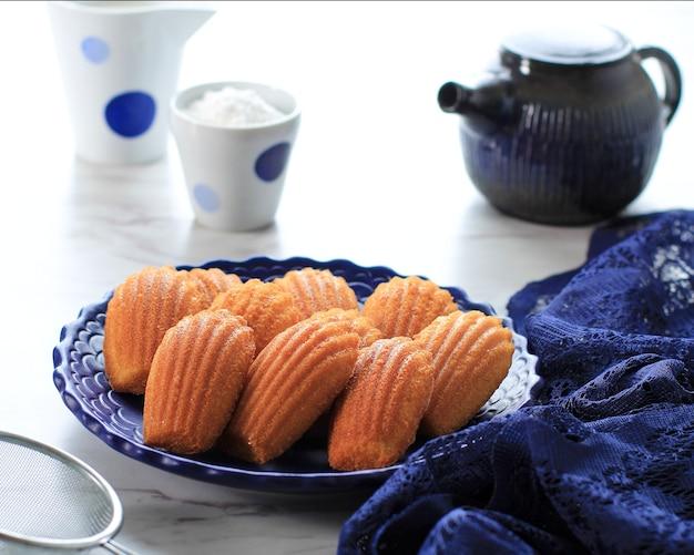 青いセラミックプレート上のバニラレモンマドレーヌ。砂糖をまぶした有名なフレンチスウィートシェルペストリー、お茶添え。お茶やコーヒーの時間に最適