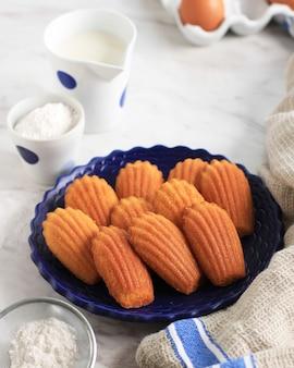 白い楕円形のセラミックプレート上のバニラマドレーヌ。有名なフレンチスウィートシェルペストリーケーキ、通常はシュガーダスティングを添えて