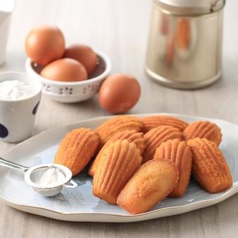 흰색 타원형 세라믹 접시에 바닐라 마들렌. 유명한 프랑스 스위트 쉘 페이스트리 케이크, 일반적으로 설탕 뿌리기