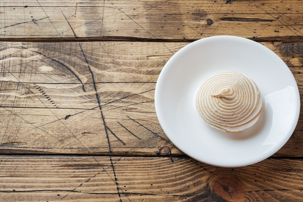 Vanilla marshmallow zephyr with caramel on a wooden table.