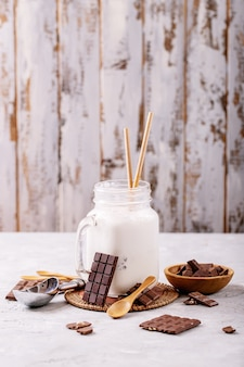 Vanilla milkshake served with chocolate over white texture background