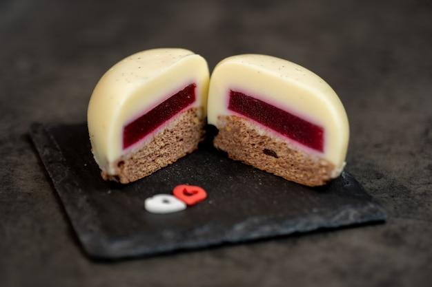 Vanilla moose cake cut in half in the shape of a heart on ardesia