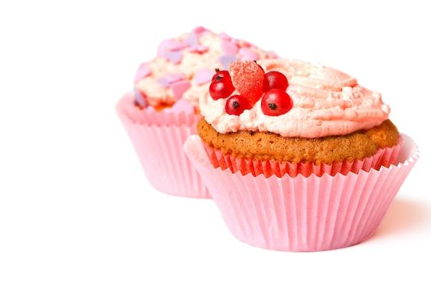 Ванильные маффины со взбитыми сливками, красной смородиной и декоративной посыпкой. фото высокого качества