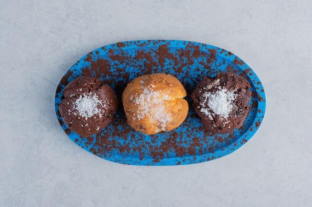 大理石の表面の大皿にバニラパウダーをトッピングしたカップケーキ