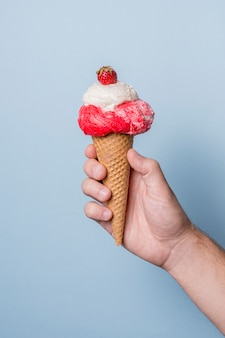 Vanilla and strawberries ice cream on cone