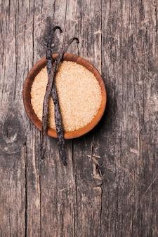 소박한 배경에 나무 그릇에 바닐라 설탕. 갈색 설탕에 바닐라 꼬투리 2개