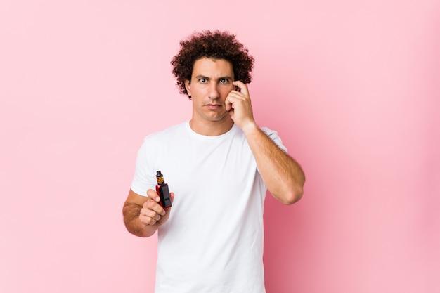 Молодой кавказский курчавый человек держа vape указывая его висок с пальцем, думая, сфокусировал на задаче.