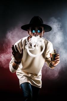 Человек делает кольцо дыма с vape