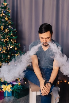 Vaper exhales steam. the guy sits near the christmas tree and smokes an electronic cigarette.