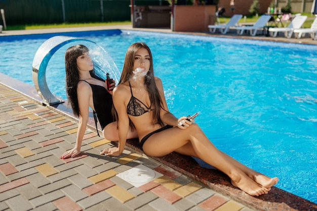 Vaping concept. beautiful two sexy girls sitting near pool and vaping electronic cigarette. close-up view.