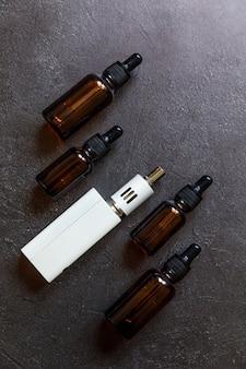 Vaping 장치 전자 담배 전자 담배 및 어두운 검은 돌 혈암 배경에 액체 병. 대체 흡연을위한 vape 장치. vaping 상점 개념. vaper에 대한 가젯. vaping 액세서리.