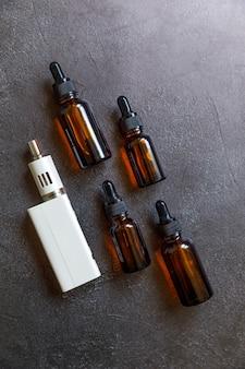 전자 담배 전자 담배와 액체 병을 어두운 검은 돌 셰일 배경에 베이핑합니다. 대체 흡연을 위한 vape 장치. vaping 상점 개념입니다. 베이퍼용 가제트. 베이핑 액세서리.
