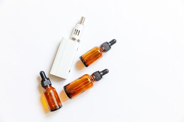 白で隔離されるvapingデバイスの電子タバコと液体ボトル
