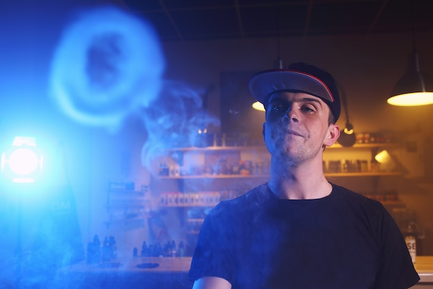 Vaping man in a cloud of vapor in a vape bar
