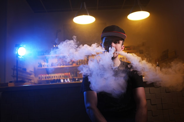Vaping man holding a mod. a cloud of vapor at the vape shop.