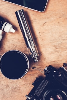Vaping set, vintage camera, smartphone and coffee on the wood table