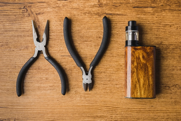 Vaping tools with wood background and mod