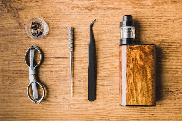 Vaping tools with wood background, scisors, atomizer, coil, mod