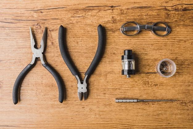 나무 배경, 가위, 분무기, 코일을 가진 vaping 도구
