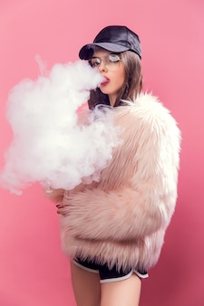 Vaping woman on pink