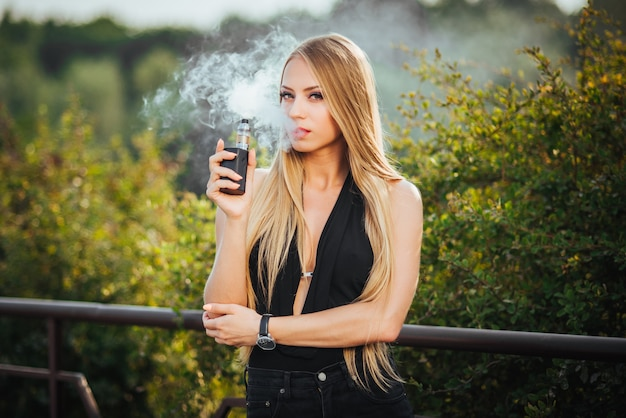 Vaping. young beautiful woman smoking e-cigarette with smoke outdoors.
