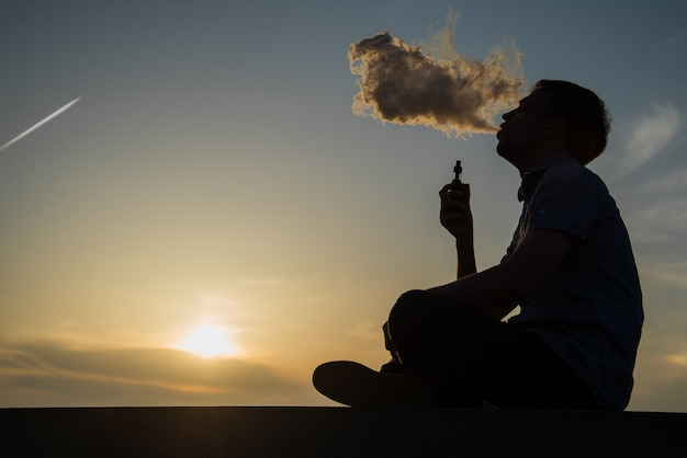 Vaping young man with, produces vapor on sunset sky background at the sea coast promenade, place for text