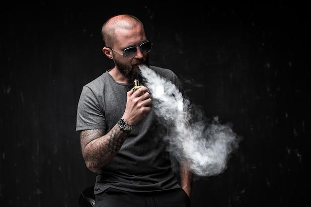 サングラスvapingのひげを持つ男性。