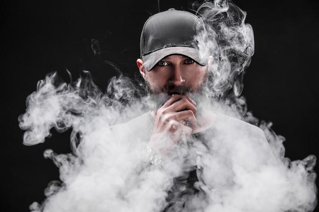 灰色のシャツに身を包んだひげを生やした男性、サングラス、野球帽vaping