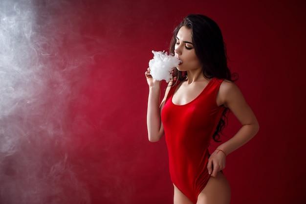 若いセクシーな女性がvapingです。蒸気の雲。スタジオ撮影。