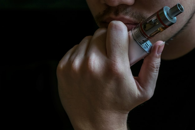 Человек со скрытой личностью, курящий противоречивую форму электронной сигареты. vaping является спорным в сообществе здравоохранения, если он безопасен или опасен для здоровья