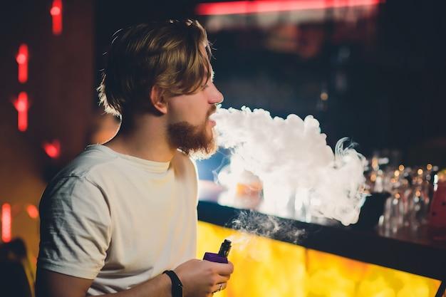 Молодой красивый битник человек с бородой, сидя в кафе с чашкой кофе, vaping и выпускает облако пара.