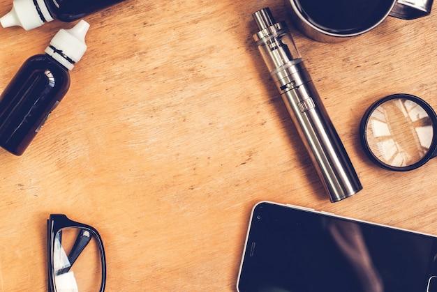 Vapingセット、スマートフォン、木製のテーブルの上のコーヒー