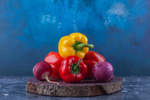 Variazione di peperoni e ravanelli di colore diverso sul pezzo di legno