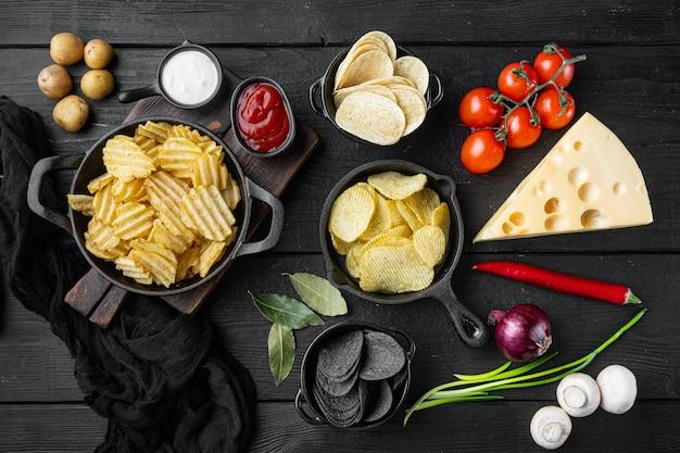チーズとオニオンをセットしたバリエーションの異なるポテトチップス、黒い木製のテーブル、上面図フラットレイ