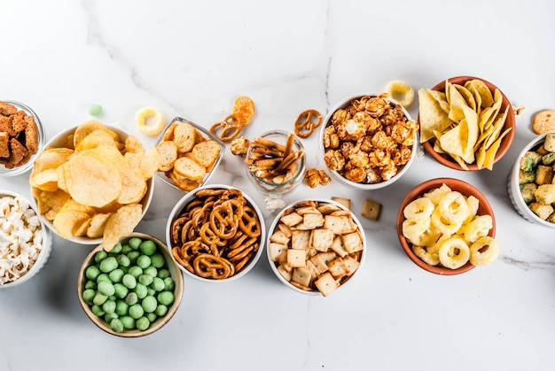 Variation different unhealthy snacks crackers, sweet salted popcorn, tortillas, nuts, straws, bretsels