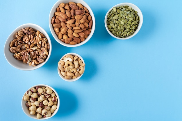Variation of nuts in bowls on blue background.