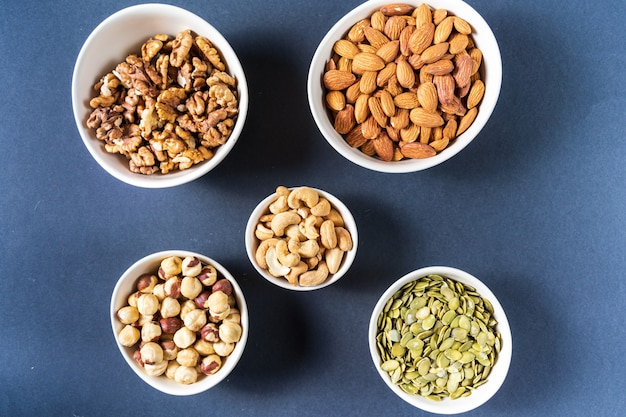 Variation of nuts in bowls on gray background.