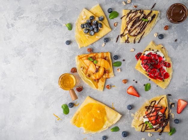 灰色のコンクリートの背景に新鮮なフルーツ、ベリー、クリームチーズ、蜂蜜、チョコレートソースのクレープや薄いパンケーキのバリエーション。上面図、コピースペース。